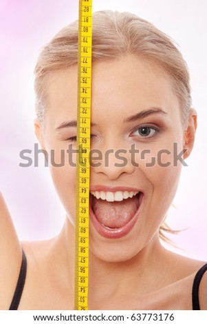Beautiful young caucasian woman with measuring tape - stock photo