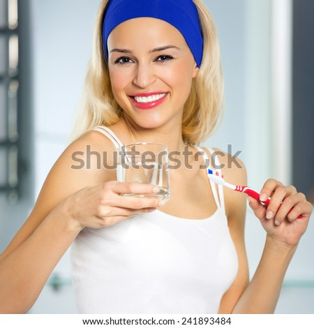 Beautiful young cheerful woman bruhing teeth - stock photo