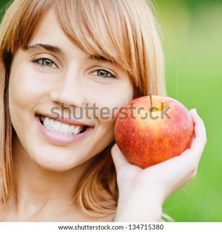 Beautiful young cheerful woman with red big apple, against green summer garden. - stock photo