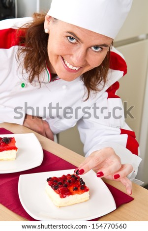 beautiful young chef decorating delicious dessert  - stock photo
