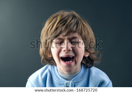 Beautiful young child crying isolated against grey background  - stock photo