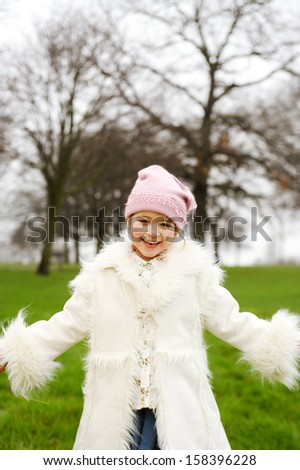 Beautiful young child girl smiling at the camera while visiting a green park during a cold winter day outdoors, wearing a furry coat and a pink woolly hat. - stock photo