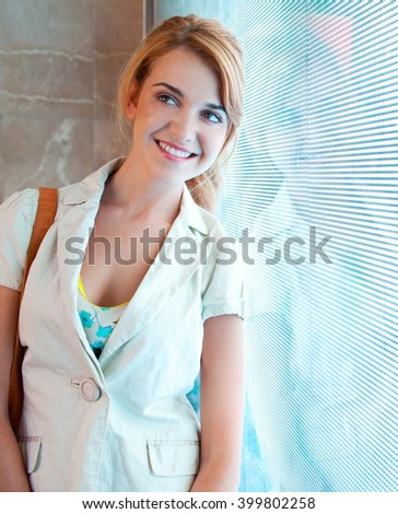 Beautiful young consumer woman leaning on a digital led lights screen in a shopping mall looking away thoughtful, smiling indoors. Joyful portrait of attractive woman by shop window, lifestyle. - stock photo