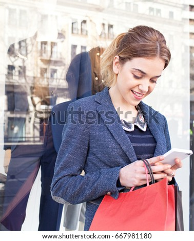 Beautiful young consumer woman using smart phone in shopping street with manikins in window with city reflections, carrying shopping bags, smiling. Female with technology recreation lifestyle.