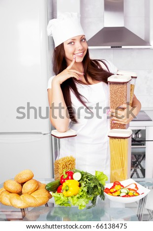 beautiful young cook with pasta and vegetables in the kitchen