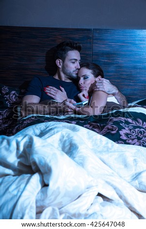 Beautiful young couple being scared in the bedroom at night. - stock photo