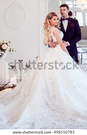 Beautiful young couple, bride and groom. Luxurious light interior
