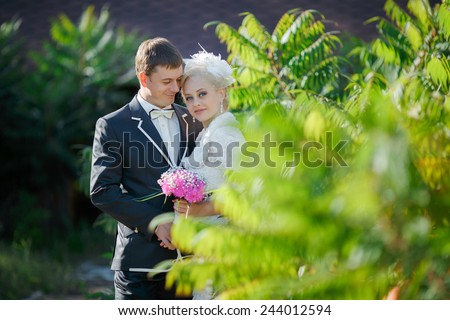 Beautiful young couple bride and groom, the European appearance, posing outdoors in the sunshine. Male groom gently embraces a woman bride's shoulders - stock photo