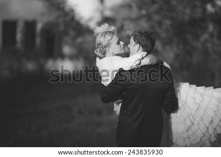 Beautiful young couple, bride and groom walk on a sunny day outdoors. The groom holds his bride in his arms and smiles of happiness