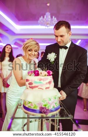 beautiful young couple cut the wedding cake - stock photo