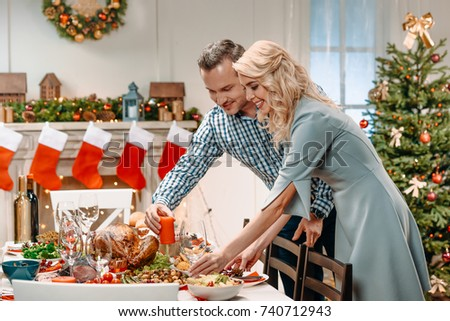 beautiful young couple decorating christmas table