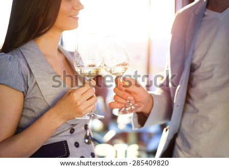 Beautiful young couple drinking wine in a bar - stock photo