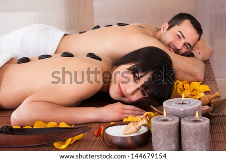 Beautiful Young Couple Enjoying Hot Stone Therapy In Spa Centre - stock photo