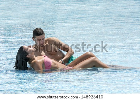 Beautiful young couple enjoying in pool on a hot summer day