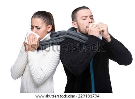 Beautiful young couple having a cold, with a scarf, isolated on white. - stock photo