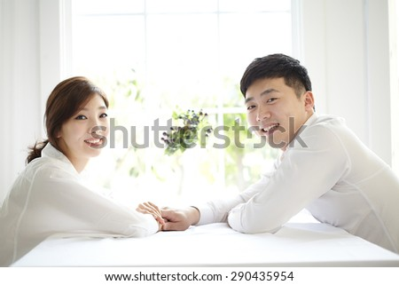 beautiful young couple having a conversation while looking at each other over a window background in a bright room - stock photo