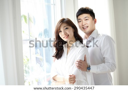 beautiful young couple having a pleasant conversation while looking out a window in a bright room