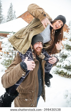 Beautiful young couple having fun and showing rock gesture in winter