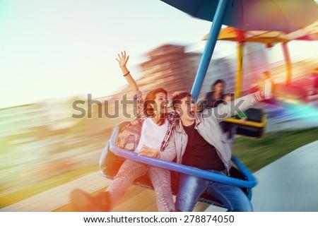 Beautiful, young couple having fun at an amusement park - stock photo