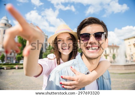 Beautiful young couple having fun together on sunny day outdoors, woman pointing away.