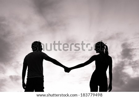Beautiful young couple holding hands during sunset. - stock photo