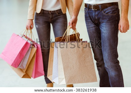 Beautiful young couple holding shopping bags while standing in mall, close-up - stock photo