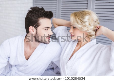 beautiful young couple in bathrobes looking at each other in bedroom