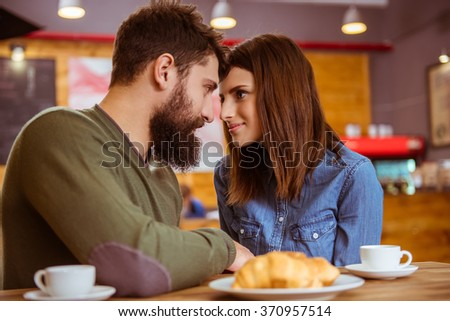 Beautiful young couple in casual clothes drinking coffee and looking at each other while sitting in a cafe - stock photo