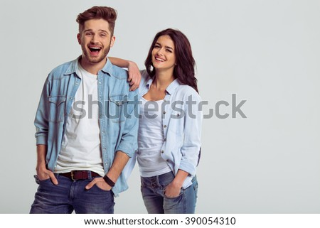 Beautiful young couple in jeans is smiling and looking at camera, on a gray background. Girl is leaning on young man - stock photo