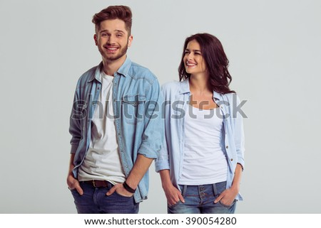 Beautiful young couple in jeans is smiling and posing, on a gray background. Girl is looking at young man - stock photo