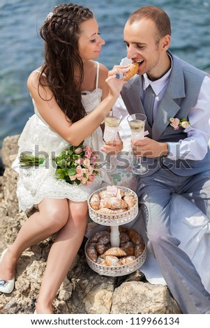 beautiful young couple in love bride and groom celebrating their wedding day on the cliffs by the sea with champagne and croissants. Series.