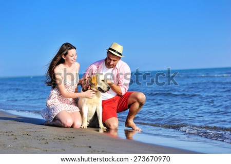 Beautiful young couple in love enjoying and having fun at the beach with their dog - stock photo