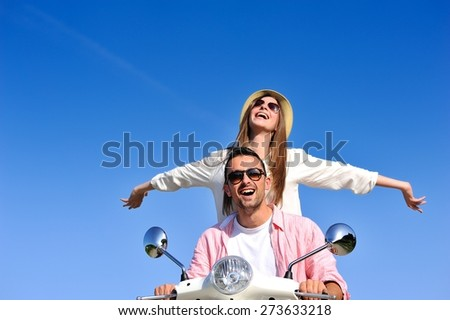 Beautiful young couple in love enjoying and having fun riding on a scooter in a beautiful nature - stock photo