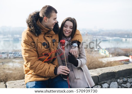 Beautiful young couple in love enjoying together and hugging, while man giving a heart to his girlfriend.