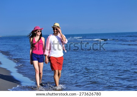 Beautiful young couple in love enjoying walking and running on the beach