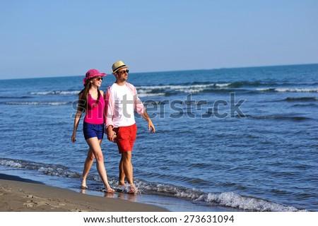 Beautiful young couple in love enjoying walking on the beach - stock photo