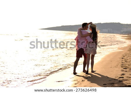 Beautiful young couple in love enjoying walking on the beach at sunset - stock photo