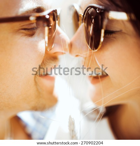 beautiful young couple in love girl and man in sunglasses and bright clothing embracing and kissing in wheat field - stock photo