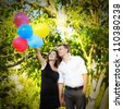 beautiful young couple  in love holding a bunch of balloons in the park - stock photo