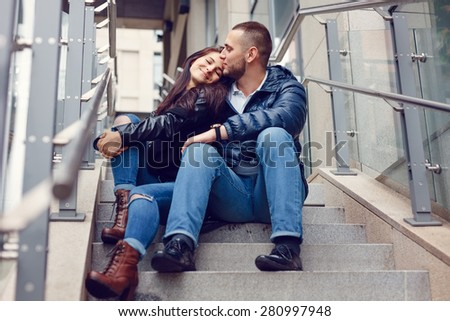 Beautiful young couple in love on a date outdoors on modern urban background. Smiling and hugging. Bearded handsome man and brunette pretty woman in casual dress. - stock photo
