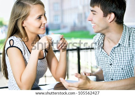 Beautiful young couple in love sitting at cafe