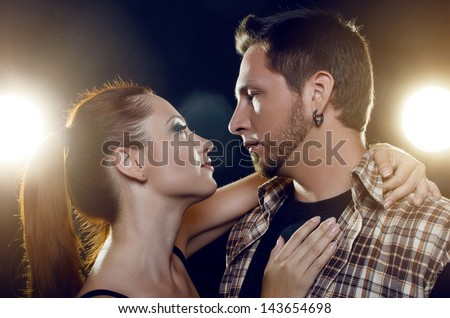 Beautiful young couple in love. The girl embraces the guy's neck and they look into each other's eyes on a black background - stock photo
