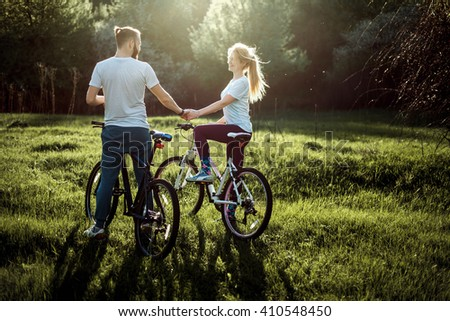 Beautiful young couple in love walking with bicycles, holding hands and talking. Stand near the bikes. The concept of active rest - stock photo