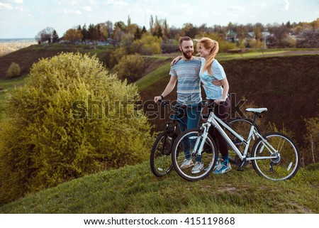 Beautiful young couple in love walking with bicycles hugging and looking at each other. The concept of joy and happiness - stock photo