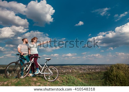 Beautiful young couple in love walking with bicycles, looking towards the beautiful nature and the blue sky. The concept of active rest