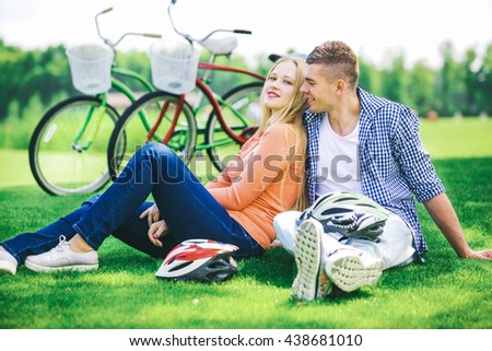 Beautiful young couple in love walking with bicycles, sit under a tree and hugging. Stand near the bikes. The concept of active rest - stock photo