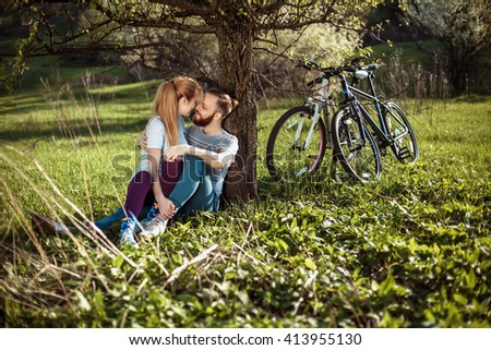 Beautiful young couple in love walking with bicycles, sit under a tree, kissing and hugging. Stand near the bikes. The concept of active rest - stock photo