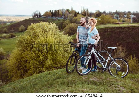 Beautiful young couple in love walking with bicycles,standing and hugging near the Bicycle and consider nature. The concept of active rest - stock photo