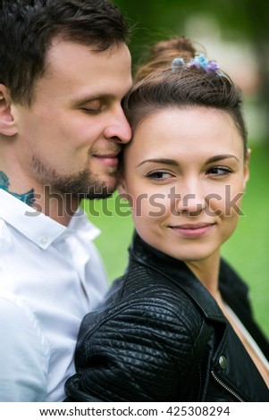 Beautiful young couple in love with tattoos hugging on the nature - stock photo
