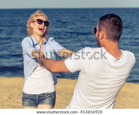 Beautiful young couple in sun glasses are holding hands, looking at each other and smiling, sunny beach in the background - stock photo